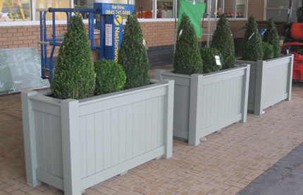 Painted wooden planter with small trees