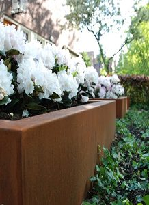 White flowers planted in a corten steel planter trough