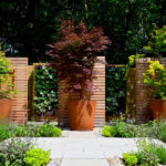 Large, round Corten Steel planters in a garden