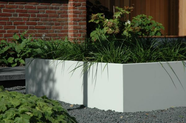 Shrubs and plants displayed outdoors in a white Aluminium planter