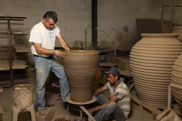 Craftsman hand building a terracotta vase