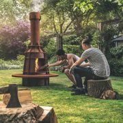 A man adding wood to a garden wood burner