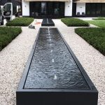 Long black water feature on a drive way