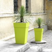 Two tall composite planters in green. Populated with small trees