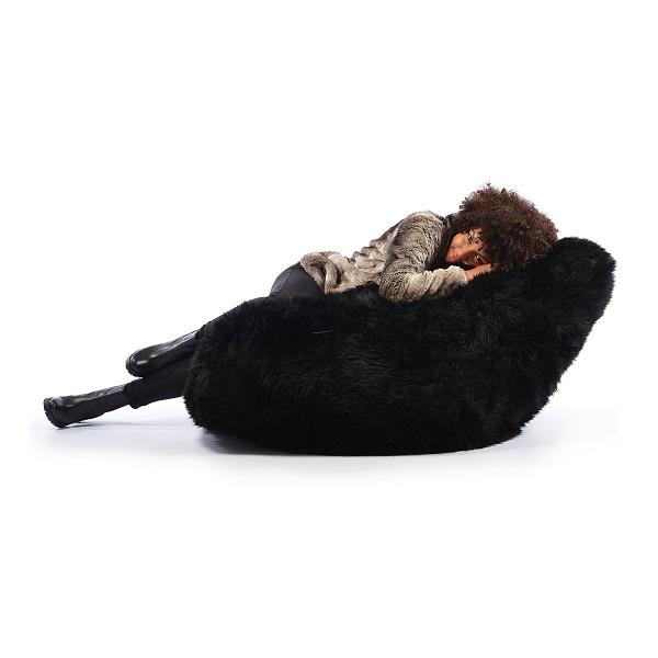 woman laying on black fur bean bag