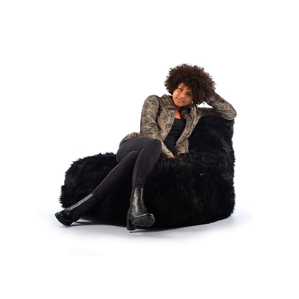 woman sitting on black fur bean bag
