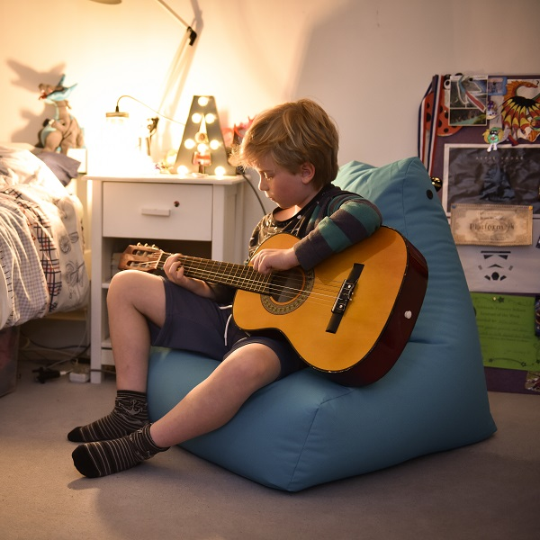 playing guitar on blue bean bag indoors